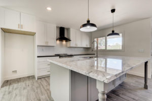 Quartz countertops, Stainless Steel Appliances, Wood Plank flooring & White & Grey Shaker Style Cabinets on the base and island
